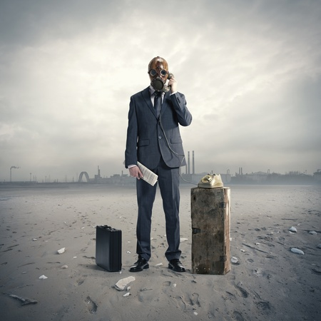 businessman with gasmask at phone Stock Photo