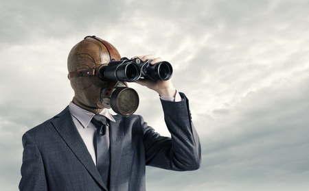 Businessman with gas mask  looking through binoculars photo