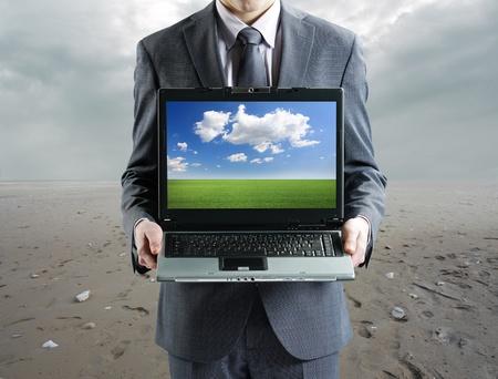 environment concept: Businessman holding his laptop photo