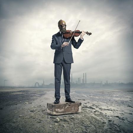 Geschäftsmann mit Gasmaske, spielt Geige Standard-Bild