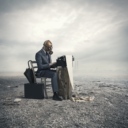 post apocalypse: business wearing a gas mask, write with an old typewriter Stock Photo