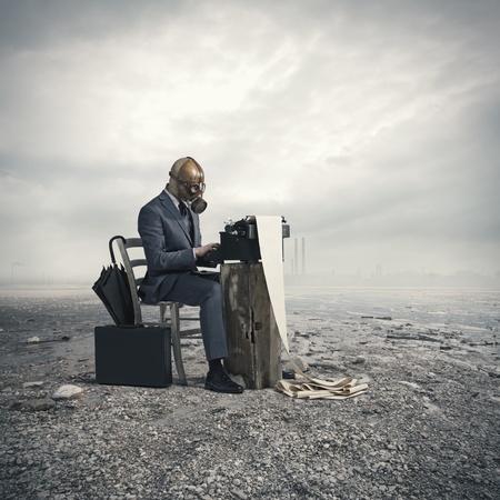 de negocios con una máscara de gas, escribir con una vieja máquina de escribir Foto de archivo