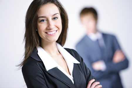 Attractive businesswoman with her arms crossed.Businessman on background Stock Photo - 13410500