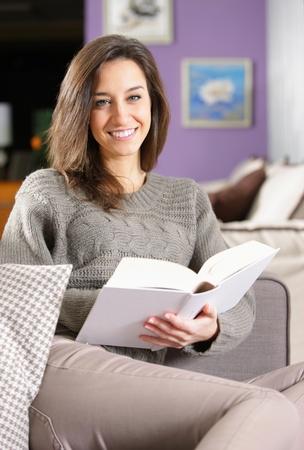 woman reading: Portrait of a happy young woman lying on couch with book