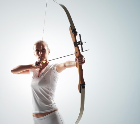 Beautiful woman aiming with bow and arrow photo