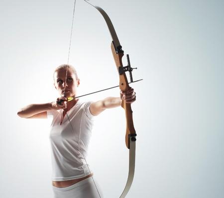 arco y flecha: Hermosa mujer apuntando con arco y flecha