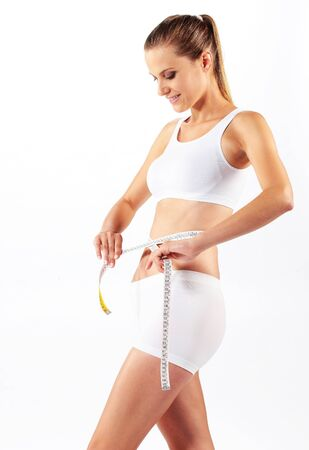 measure waist: young beautiful woman measuring her abdomen with a meter-stick Stock Photo
