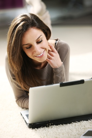 Smiling woman using her laptop in the living room. Stock Photo - 13508688