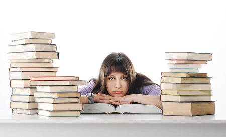 Tired of studies, young Woman is sitting on her desk with books  photo