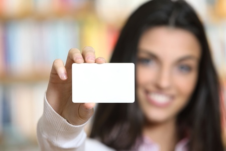 business card in hand: smiling young female showing a business card  -  copy space. Stock Photo