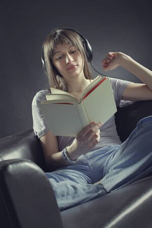 A young woman sits on a couch  reading a book and listening to music through a pair of headphones photo