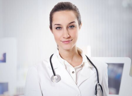 at pharmacy: portrait of  smiling young woman pharmacist with stethoscope photo