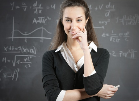 school campus: Portrait of a young woman, college student or teacher in front of a blackboard