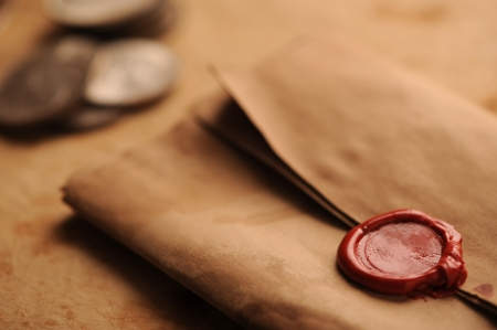 wax seal on a grunge paper, old coins on background photo