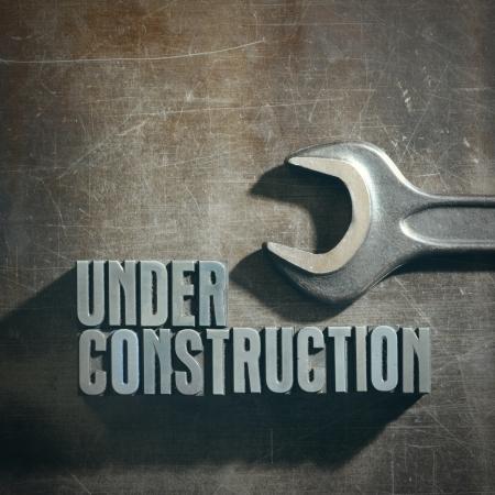 Bajo signo de construcción con una textura de fondo metálico Foto de archivo