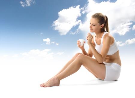 eating yogurt: Young woman eating yogurt as breakfast or snack Stock Photo