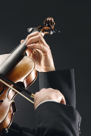 the violinist: Musician playing violin on dark background Stock Photo - 13633234