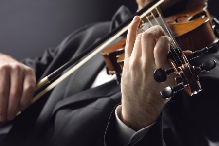 the violinist: Musician playing violin on dark background photo