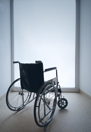 Empty wheelchair parked in hospital hallway photo