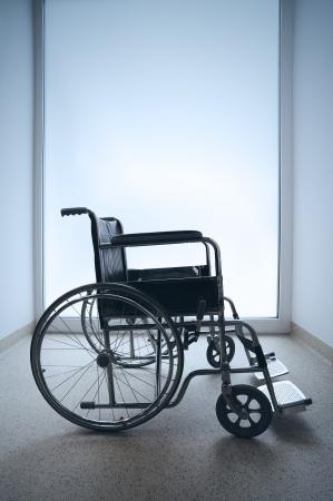 medicine wheel: Empty wheelchair parked in hospital hallway