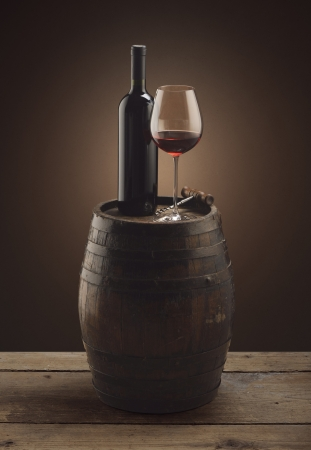 red wine bottle and wine glass on wooden barrel photo