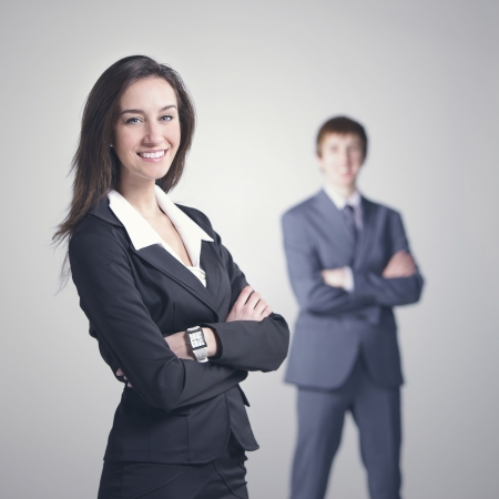 Attractive business woman with her arms crossed.Businessman on background photo