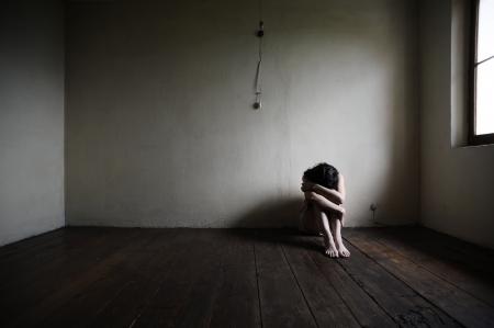 mujer llorando: triste mujer sentada sola en un cuarto vacío