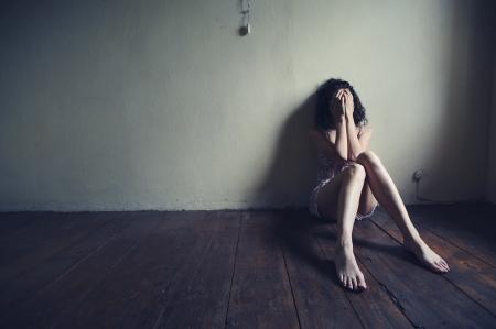 femme triste: femme triste, assise seule dans une chambre vide