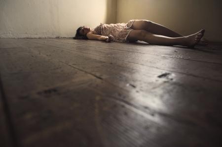 죽은: 나무 바닥에 누워 죽은 여자. 빈 방 스톡 사진
