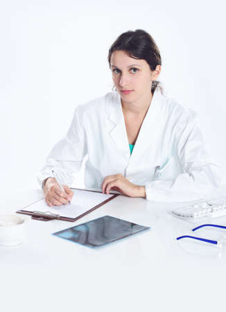 Young woman doctor  sitting on her desk , looking at camera photo