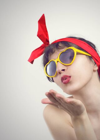 Young beautiful woman in sunglasses blow a kiss to you. photo