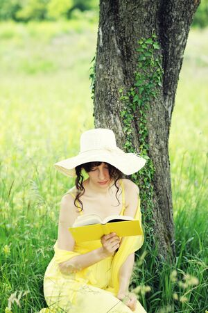 nature photography: beautiful young woman reading book at park