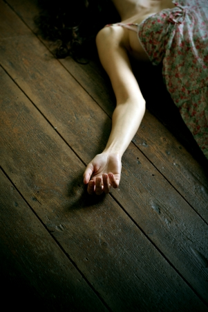 murdering: dead woman lying on the floor, focus on the hand Stock Photo