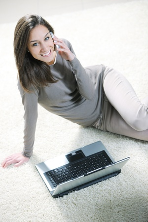 Smiling woman using her laptop in the living room. photo