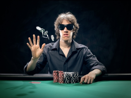 Poker player at a poker table throwing his chips photo