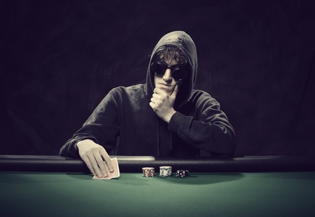 Portrait of a professional poker player sitting at a poker table photo
