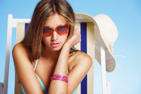 Young woman with sunglasses on beach chair Stock Photo - 14190724