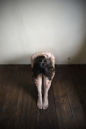 a desperate young woman is sitting on an old wooden floor. top view photo