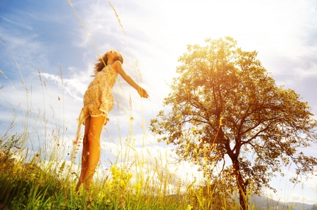 midst: Beautiful woman  in the midst of a green lawn, she looks at the sky, so carefree
