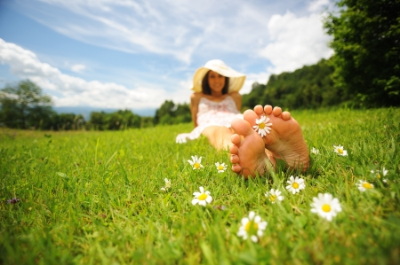 a smiling young woman is lying on a green lawn, with a daisy between her toes; shallow deep of field; selective focus; DOF photo