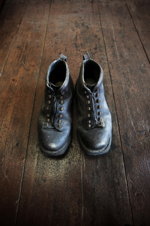 impervious: an old pair of leather boots on an old wooden floor Stock Photo