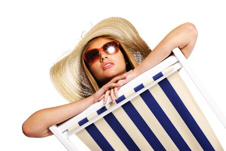 Beautiful young woman with sunglasses relaxing on beach chair isolated on white background photo