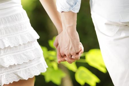 parejas caminando: un par de jóvenes amantes paseando cogidos de la mano en un parque, cerca de las manos Foto de archivo