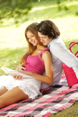 a young couple read a book together in the park photo