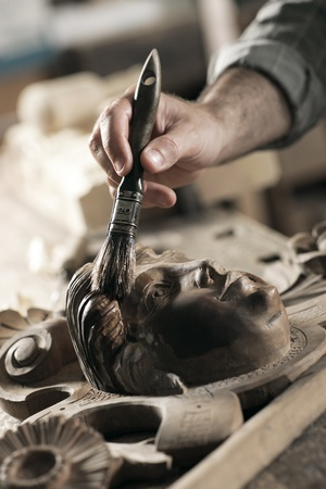 sculptor: Close Up of carpenter apply varnish to a wooden sculpture Stock Photo