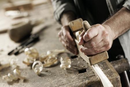 carpintero: Las manos de un carpintero de madera cepillada, lugar de trabajo