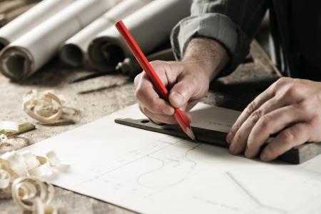 marking up: Closeup vista de un carpintero con un l�piz rojo para dibujar una l�nea en un plano Foto de archivo