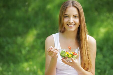 Portrait of happy beautiful young woman eating vegetable salad photo