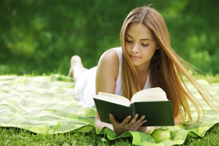 Closeup of a beautiful young woman reading book at park photo