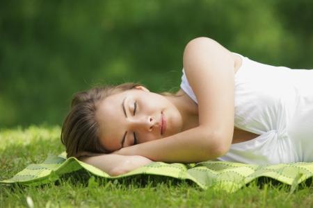 Beautiful woman lying and sleep on the grass photo